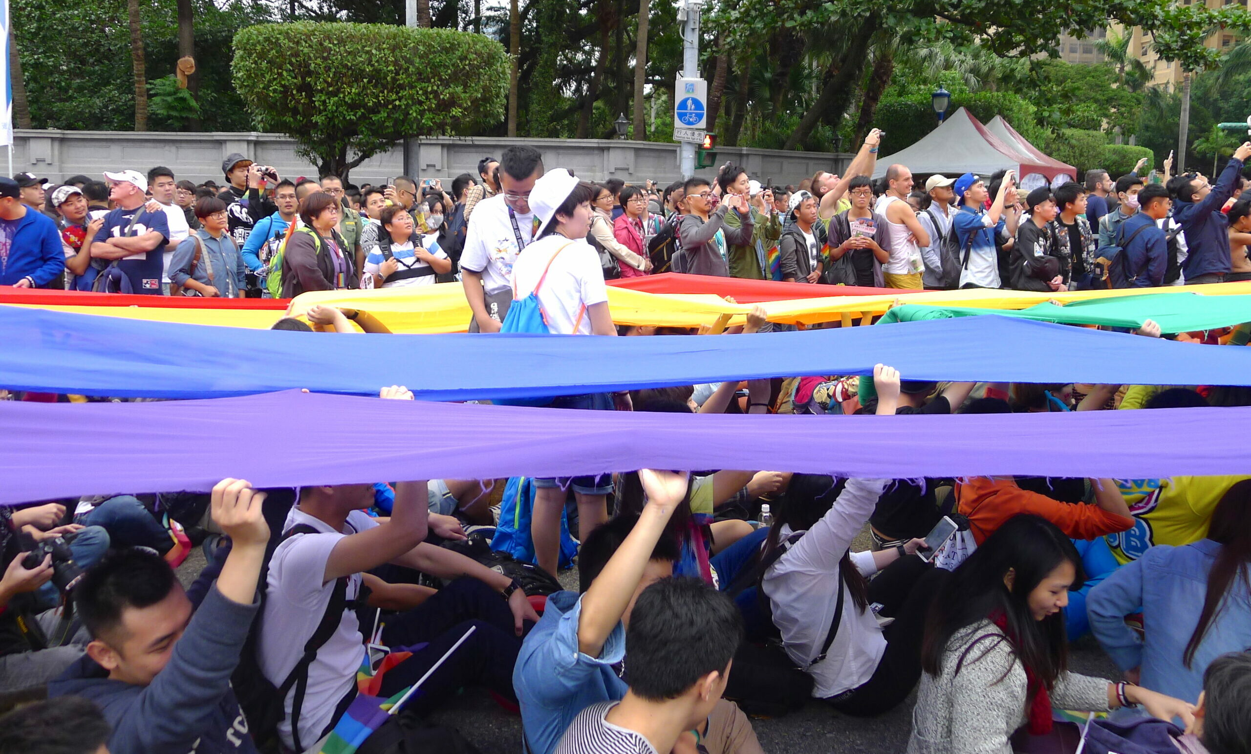 Photo from 2015 Taiwan Pride- people on the ground holding long rainbow colors fabric